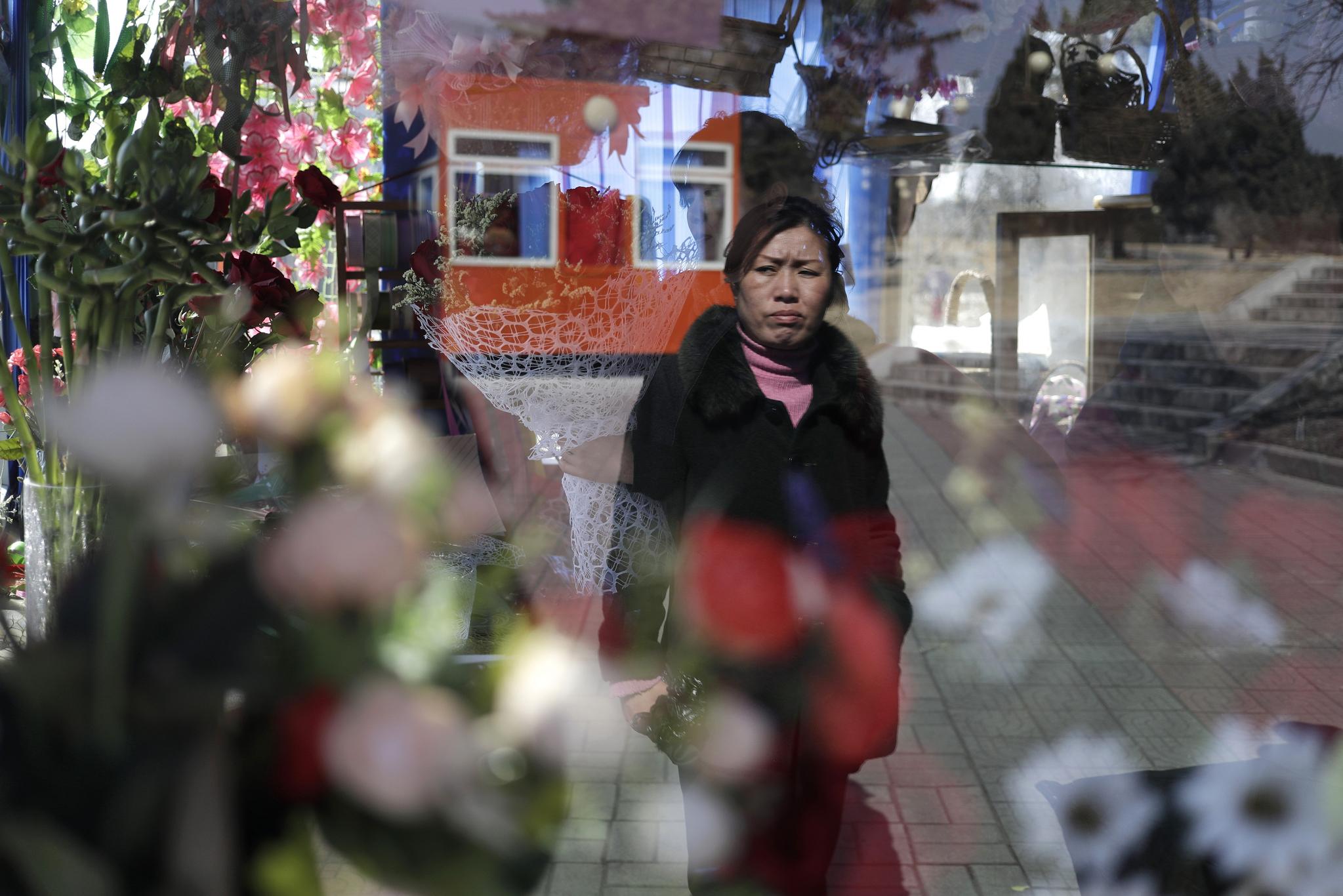 한 평양 여성이 '국제부녀절'을 맞아 선물용 꽃다발을 마련한 꽃집 앞을 지나가고 있다. [AP=연합뉴스]