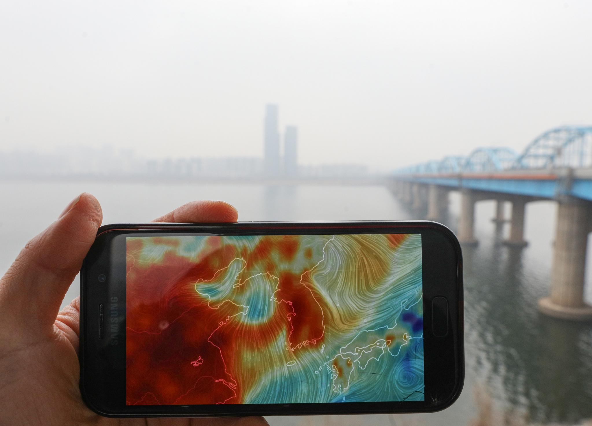 초미세먼지 주의보가 발령된 25일 오전 서울 동작대교에서 바라본 도심이 뿌옇게 보인다. 왼쪽 스마트폰 화면은 미국 국립기상청의 데이터를 기반으로 지표면의 기상 상황을 나타내는 사이트(earth.nullschool.net)에 나타난 붉은 초미세먼지(PM2.5) 표시가 한반도를 뒤덮고 있는 모습. [뉴스1]