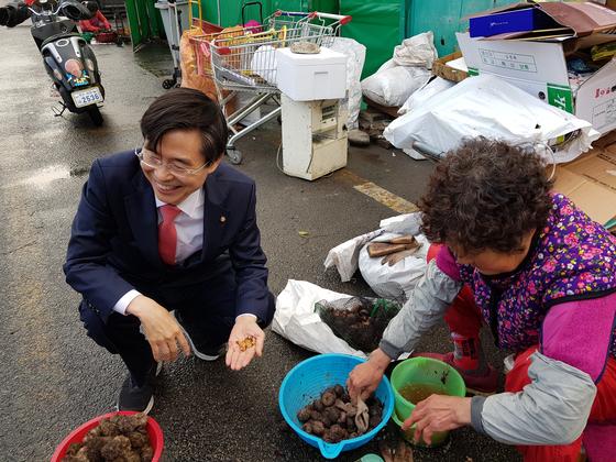 """6일 부산 다대포 어시장을 찾은 조경태 자유한국당 최고위원에게 한 상인이 성게알을 먹여주고 있다. 이날 만난 상인들은 조 의원을 """"정이 들 대로 든 사람""""이라고 표현했다. 성지원 기자"""