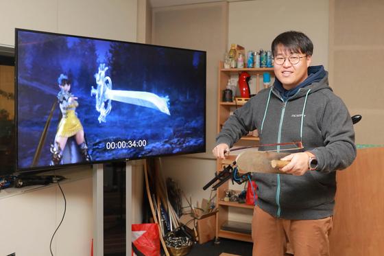 국내 유일의 게임 폴리 아티스트인 박준오씨. 화면 속 칼이 날아가는 소리를 바이올린 활과 미장용 흙손을 문질러 재연하고 있다. [사진 엔씨소프트]