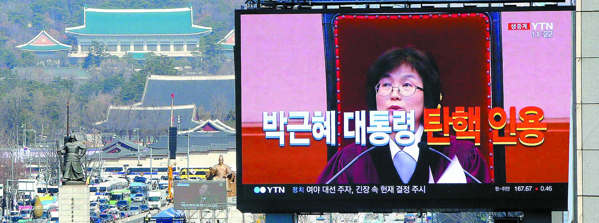 2017년 3월 10일 이정미 헌재소장 권한대행이 서울시 재동 헌법재판소 대심판정에서 박근혜 대통령 탄핵심판 사건에 대해 탄핵 인용을 선고하고 있다. 같은 시간 촛불집회가 열리던 광화문광장 너머로 청와대가 보인다. [중앙포토]