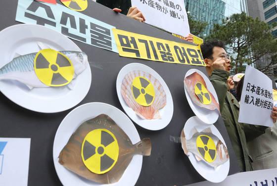지난해 3월 19일 서울 종로구 옛 일본대사관 터 앞에서 열린 '일본산 식품 수입규제 WTO 패소 대응 촉구 기자회견'에서 참가자들이 후쿠시마 방사능 오염 수산물 수입에 반대하며 구호를 외치고 있다.[연합뉴스]