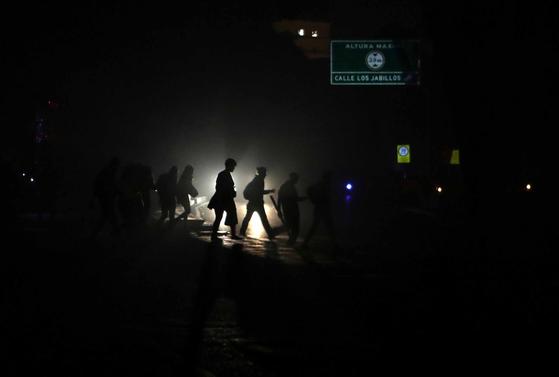 지난 8일 새벽 정전으로 암흑이 된 베네수엘라 카라카스 거리를 행인들이 지나가고 있다. [EPA=연합뉴스]