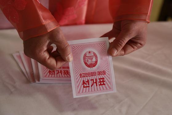 북한의 제14기 최고인민회의 대의원 선거가 10일 치러졌다. 선거관리원이 평양의 한 투표소에서 투표용지를 보여주고 있다.[AP=연합뉴스]
