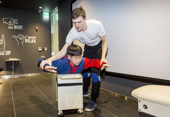 러시아 코치 디마가 플라이베드 위에 자세를 취한 한승민 학생기자에게 플라잉 자세를 가르쳐주고 있다.