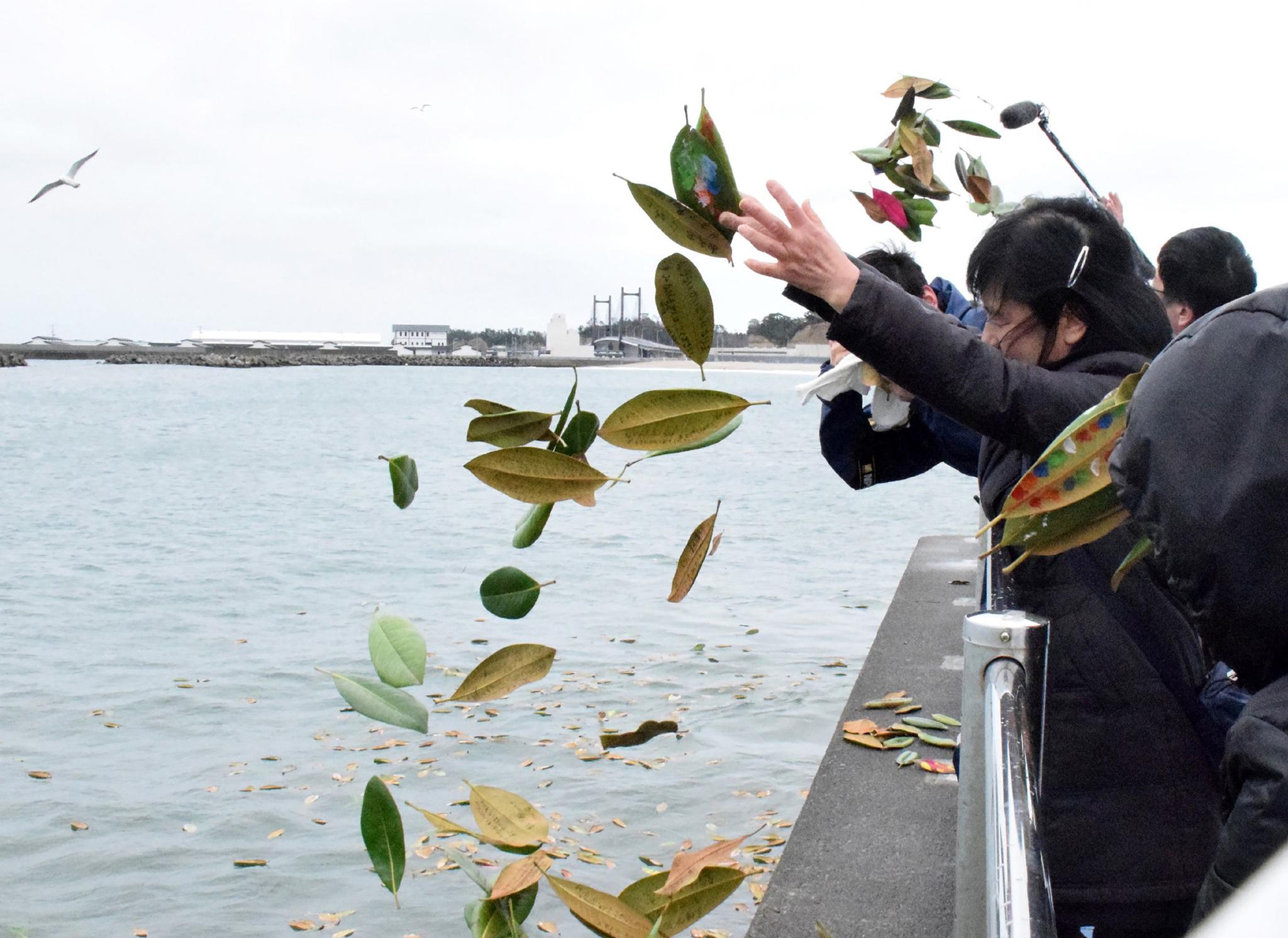 """동일본 대지진으로 458명이 사망한 후쿠시마현 소우마시의 연안에서 지진 발생과 함께 이어진 쓰나미로 가족을 잃은 유족들이 """"잊지 않을께요"""" 등의 추도 문구가 적힌 목련잎을 바다에 흘려 보내고 있다. [지지통신]"""