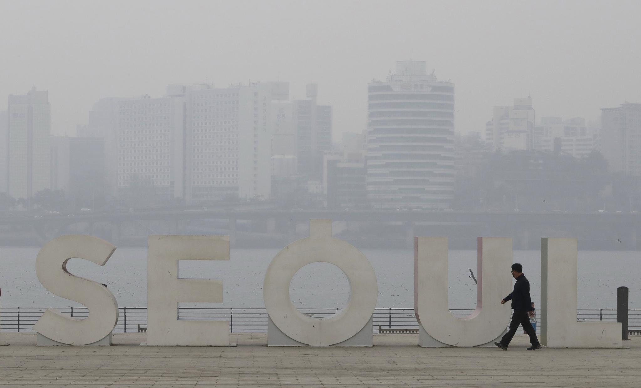 한 서울시민이 마스크를 끼고 먼지 자육한 한강변을 산책하고 있다. [AP=연합뉴스]