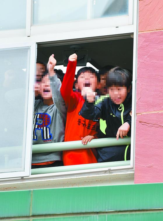 """광주시 동구의 한 초등학교 학생들(왼쪽)이 11일 오후 광주지방법원에 출석하는 전두환 전 대통령을 향해 '전두환은 물러가라""""고 외치고 있다. [뉴스1]"""