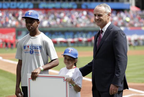 롭 맨프레드(오른쪽) MLB 커미셔너가 지난해 3월 텍사스 -휴스턴 의 개막전에서 유스 아카데미에 참가한 어린 선수들과 기념사진을 찍고 있다. [AP=연합뉴스]