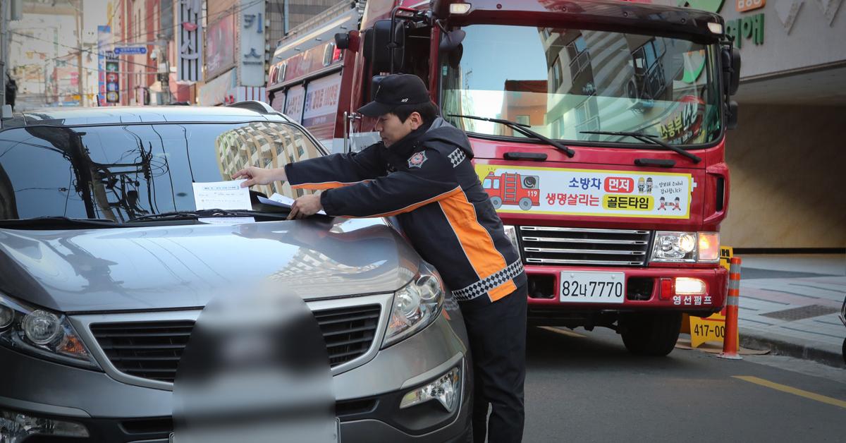 한 소방관이 불법정차 차량에 안내문을 부착하고 있다. [중앙포토]