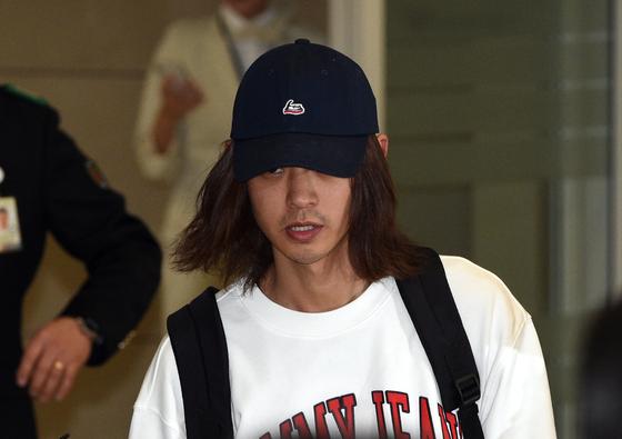 이성과의 성관계를 불법 촬영해 유포한 혐의로 입건된 가수 정준영(30)이 12일 오후 인천국제공항을 통해 귀국하고 있다. [뉴스1]