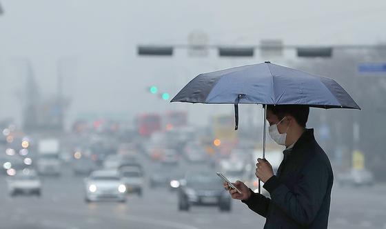 서울 및 수도권 지역에 초미세먼지 주의보가 발령된 12일 오전 서울 여의도에서 마스크와 우산을 쓴 시민이 발걸음을 옮기고 있다. [뉴스1]