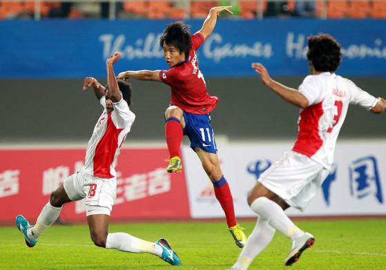 2010년 11월 중국 광저우 티엔허 경기장에서 열린 아시안게임 한국과 아랍에미레이트의 준결승전에서 조영철이 수비를 피해 슛을 날리고 있다.[중앙포토]