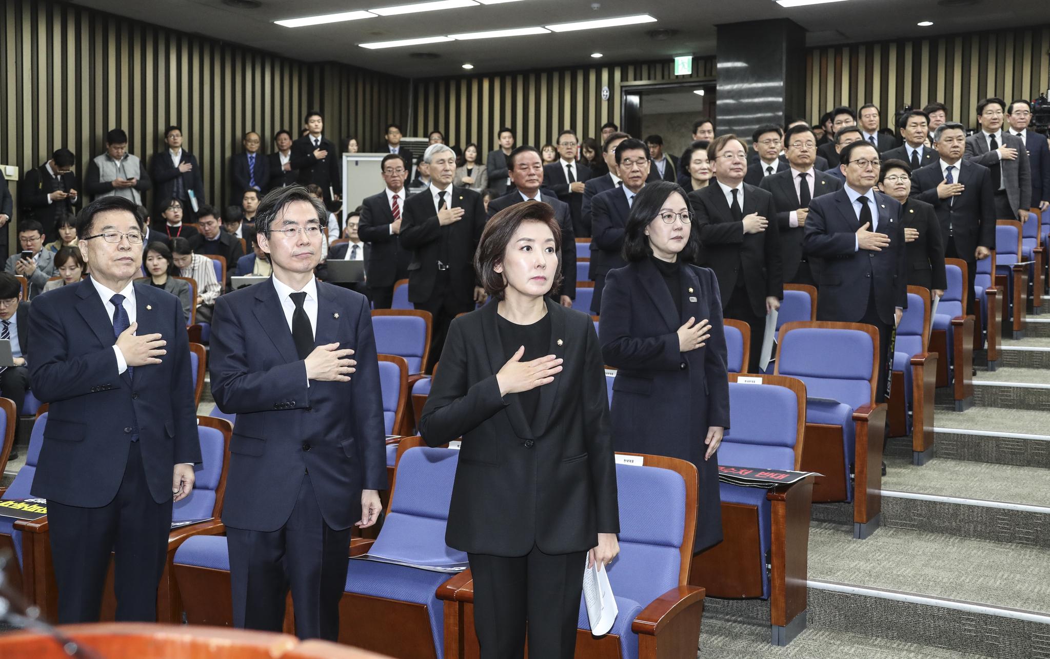 자유한국당 나경원 원내대표(가운데)와 의원들이 15일 오전 국회에서 열린 긴급 의원총회에서 국민의례를 하고 있다.  임현동 기자