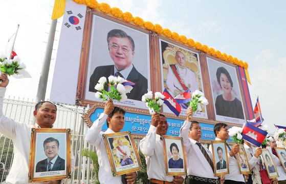 캄보디아를 국빈 방문 중인 문재인 대통령이 14일(현지시각) 오후 프놈펜 국제공항에 도착하자 프놈펜 시민들이 사진과 조화를 들고 환영하고 있다. [청와대사진기자단]