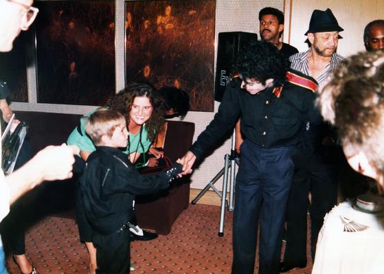 1987년 어린 웨이드 롭슨이 마이클 잭슨과 악수하고 있는 모습. HBO에서 방영된 '네버랜드를 떠나며' 다큐멘터리 속 한 장면이다. [사진 HBO via AP]