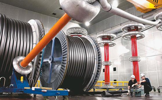 LS전선의 직원들이 500kV 초고압직류송전(HVDC) 케이블을 테스트하고 있다. LS전선은 HVDC 케이블을 국산화해 덴마크의 해저 케이블 프로젝트에 수출한 데 이어 올해는 친환경적이고 에너지 효율을 높일 수 있는 기술 개발에 박차를 가하고 있다. [사진 LS그룹]