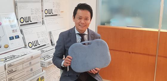 엑스젤을 만든 카지 코퍼레이션 창업자의 아들인 오가와 카나메 CEO가자사의 대표 상품인 '아울(부엉이)' 방석을 들고 웃고 있다. [김경진 기자]