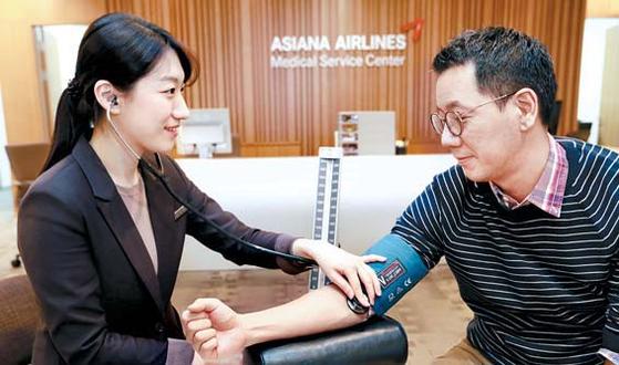 아시아나항공은 행복한 직장문화 조성을 위해 임직원의 건강 관리에 최선을 다하고 있다. 직원이 사내 의료서비스팀에서 혈압을 재고 있는 모습. [사진 아시아나항공]