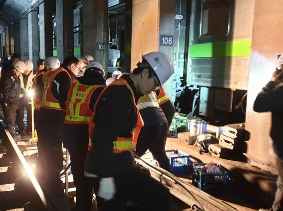 지난 14일 지하철 7호선 도봉산역으로 이어지는 터널에서 발생한 열차 탈선 사고 현장에서 관계자들이 탈선된 열차를 복구하고 있다. [연합뉴스]