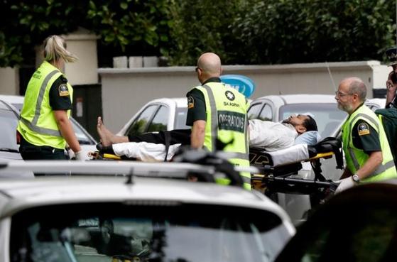 대규모 총기난사 사건이 발생한 뉴질랜드 크라이스트처치 중심부에서 15일 구급대원들이 부상자를 옮기고 있다. [AP=뉴시스]
