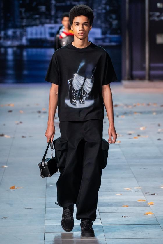 루이비통 2019 가을 겨울 남성복 쇼. 마이클 잭슨의 트레이드마크인 흰 양말과 검정색 신발이 프린트된 티셔츠를 입은 모델이 걸어 나오고 있다.