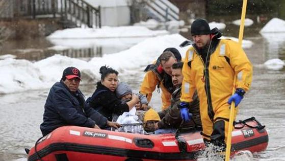 겨울철 이상 기상현상인 '폭탄 사이클론'으로 홍수가 발생한 미국 위스콘신주 그린베이에서 15일 소방대원들이 주민들을 대피시키고 있다. [AP=연합뉴스]