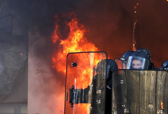 프랑스 파리에서 노란 조끼 시위대가 불을 지른 건물 앞에 경찰들이 서 있다. [AP=연합뉴스]