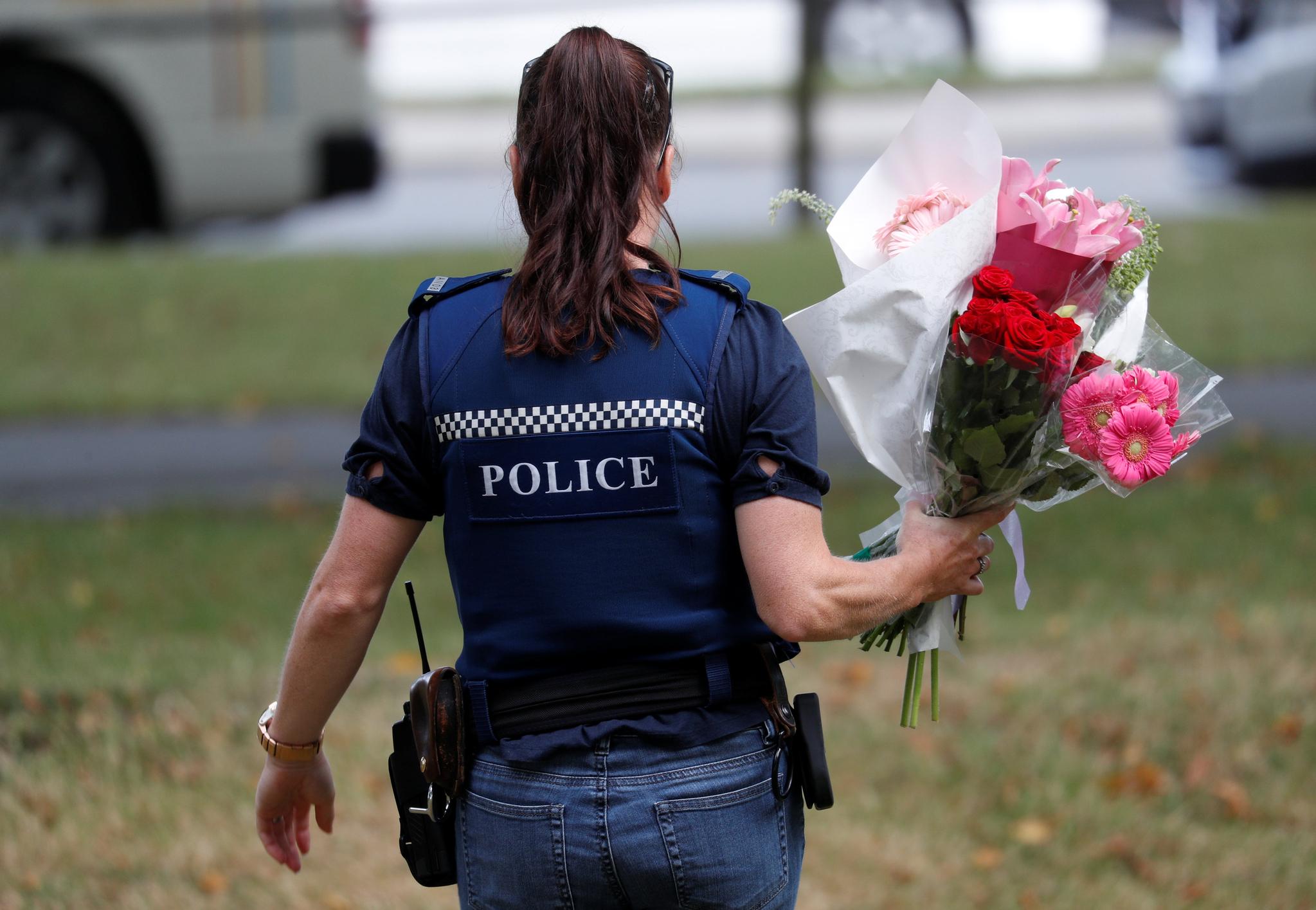 한 경찰이 17일(현지시간) 주민들이 건넨 추모 꽃다발을 들고 있다. [로이터=연합뉴스]