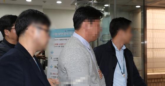'버닝썬-경찰 유착 고리'로 지목된 전직 강남경찰서 경찰 강모(44·가운데)씨. [연합뉴스]