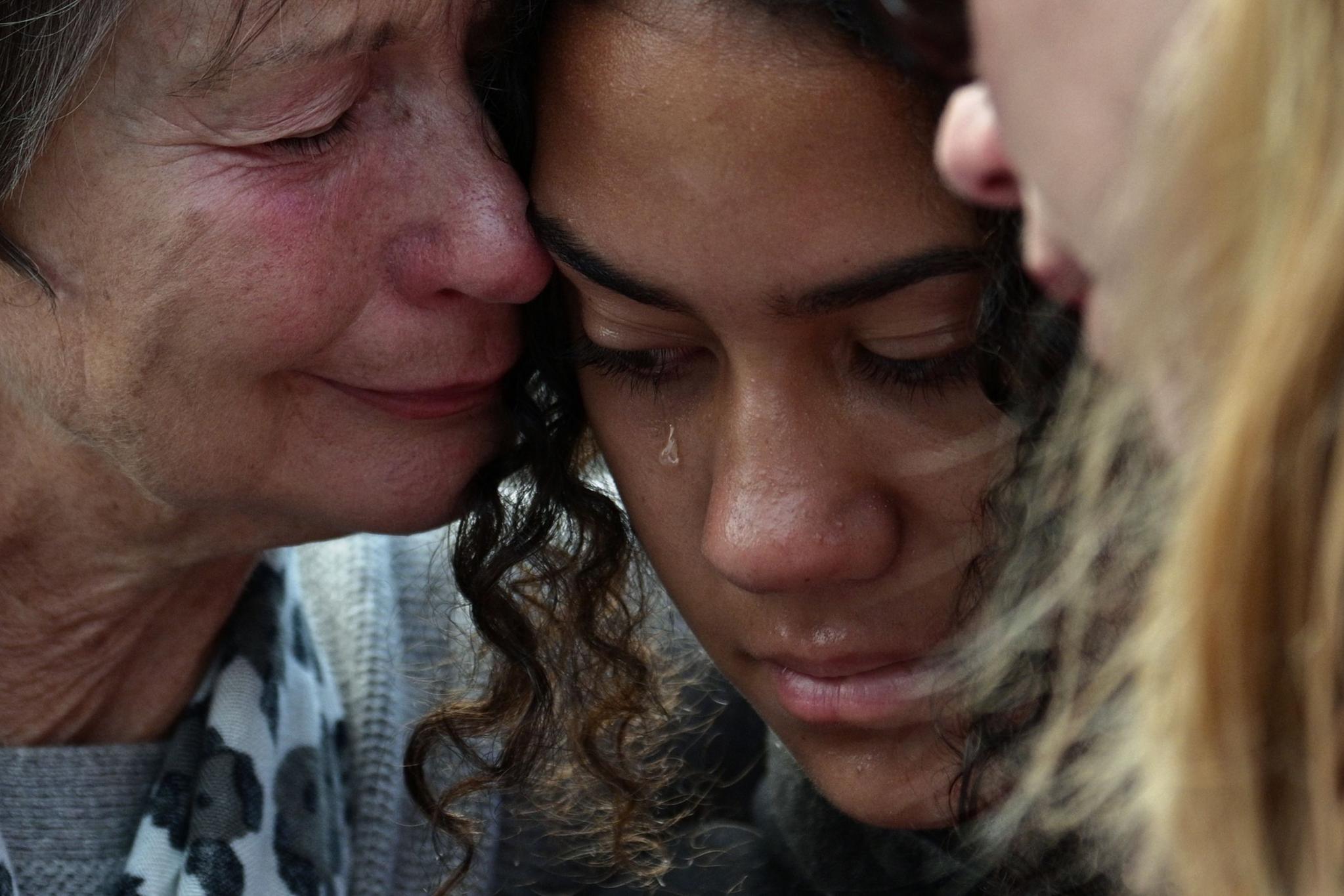 17일(현지시간) 뉴질랜드 크라이스트처치의 사건 현장 인근에 사는 주민들이 희생자 추모 꽃다발을 놓은 뒤 눈물을 흘리고 있다. [AFP=연합뉴스]
