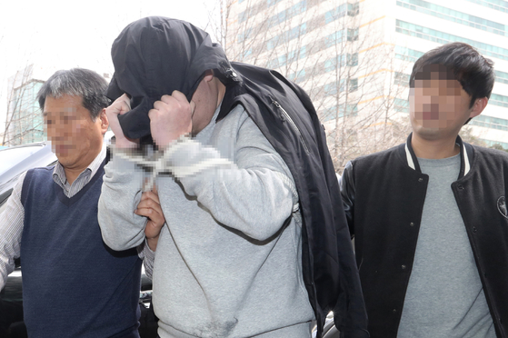 '청담동 주식 부자' 이희진 씨 부모 살해 용의자 김모(34) 씨가 18일 오전 경기도 안양시 동안경찰서에서 조사를 받기 위해 이동하고 있다. 경찰은 나머지 용의자 3명을 쫓고 있다. [연합뉴스]