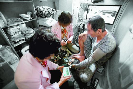 '찾아가는 동주민센터'(찾동) 사업에 참여한 복지 플래너와 방문 간호사가 서울 방학3동에 있는 독거 어르신의 집을 방문해 건강 검진을 하고 있다. [사진 서울시]