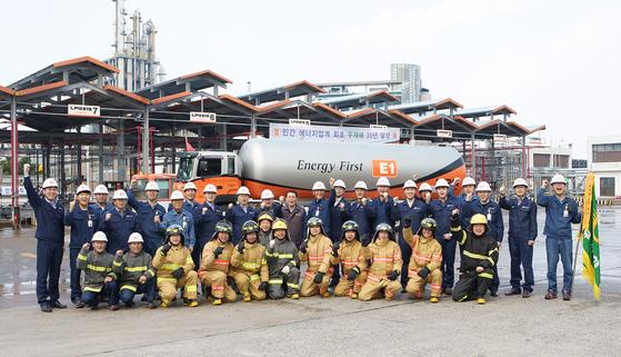 구자용 회장(뒷줄 가운데)과 E1 임직원들이 지난 15일 여수기지에서 안전사고 대응 훈련을 실시하고, 무재해 35년 달성 기념 촬영을 하고 있다. [사진 E1]