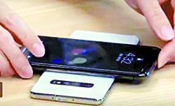 이두희씨가 갤럭시S10 플러스 뒷면에 자신의 아이폰X을 대고 배터리 충전을 하고 있다.