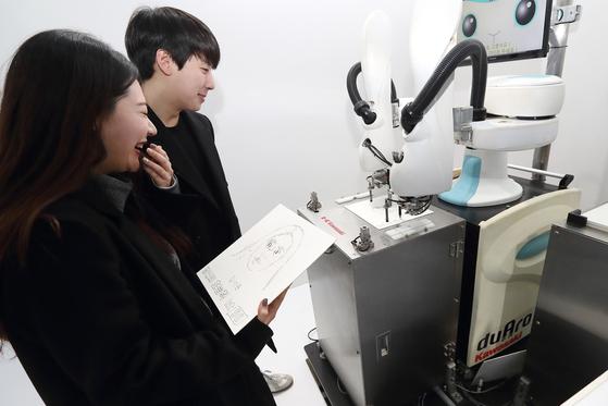 KT가 서울 광화문 광장에 연 5G 체험관에서 15일 방문객들이 로봇화가가 초상화를 그리는 모습을 지켜고 있다. [연합뉴스]