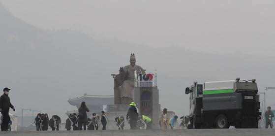 초미세먼지 주의보가 발령된 20일 오전 서울 광화문광장에서 서울시·종로구 직원들과 시민들이 미세먼지 제거 물청소를 하고 있다. [연합뉴스]