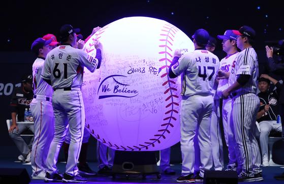 10개 구단 주장들이 팬들의 소망이 적힌 대형 야구공에 사인을 하고 있다. [연합뉴스]