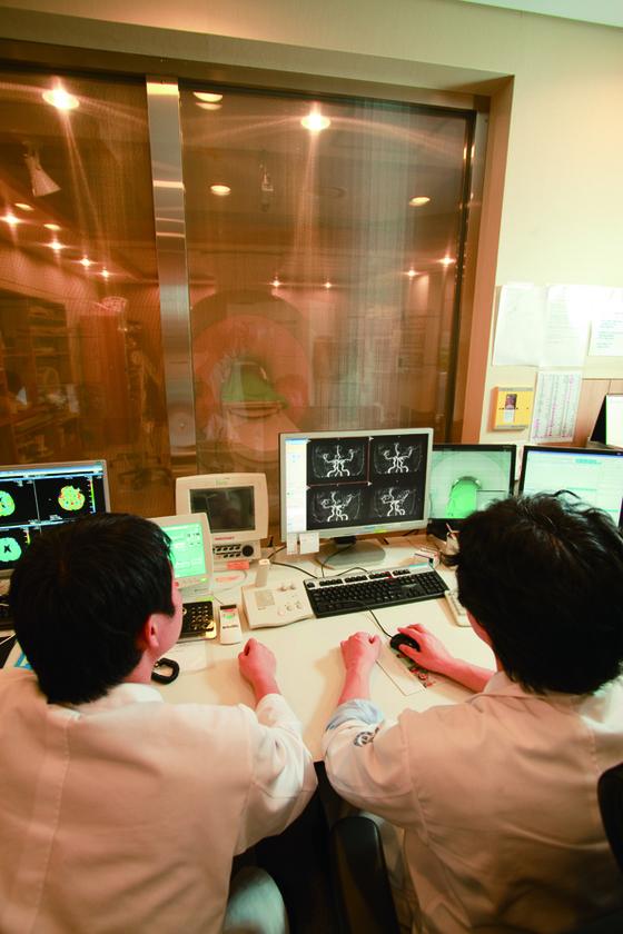 세브란스병원 의료진이 치매 환자에게 뇌 자기공명영상촬영(MRI) 검사를 하고 있다. [중앙포토]