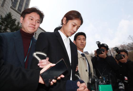 성관계 동영상을 불법적으로 촬영·유통한 혐의를 받는 가수 정준영이 21일 서울중앙지법에서 열린 구속 전 피의자 심문(영장실질심사)을 마치고 법정 밖으로 나서고 있다. [연합뉴스]