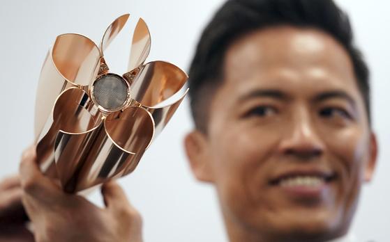 지난 20일 도쿄에서 올림픽 금메달리스트인 유도선수 노무라 타다히로가 '2020 도쿄올림픽' 성화 봉송에 사용할 토치를 들어 보이고 있다. 상부 디자인은 벚꽃잎을 본땄다. [AP=연합뉴스]