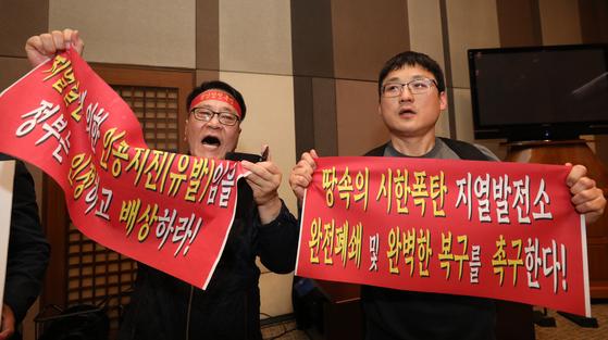 20일 오전 서울 중구 프레스센터에서 정부조사연구단의 발표를 앞두고 포항지진 시민연대 회원들이 지열발전에 의한 '유발지진'임을 주장하며 정부의 사과와 보상을 촉구하고 있다. [뉴스1]