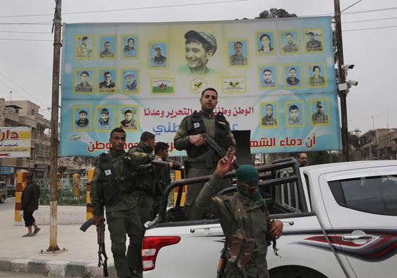 쿠르드 근거지인 시리아 북부 알레포주 도시 만비즈에서 쿠르드 전사들이 무장한 채 차량에 올라 포즈를 취하고 있다. [AP=연합뉴스]