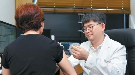 한 60대 여성이 독감 백신 주사를 맞고 있다. 접종 후 약 한 달이 지나야 효과가 나타나기 때문에 독감이 유행하기 전에 미리 접종해야 한다. 프리랜서 인성욱