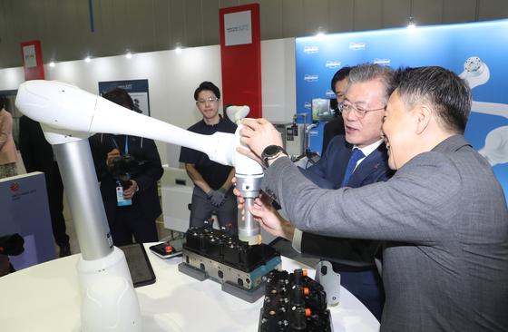 문재인 대통령이 22일 오전 '로봇산업육성 전략보고회'가 열린 대구 달성군 현대로보틱스에서 현장 관계자와 로봇을 이용한 작업을 시연하고 있다. [연합뉴스]