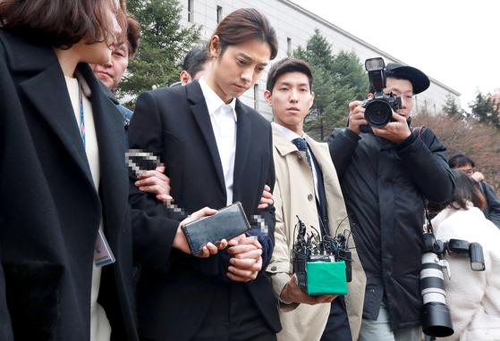 성관계 동영상을 불법적으로 촬영·유포한 혐의를 받는 가수 정준영이 21일 오후 서울중앙지법에서 열린 구속 영장실질심사를 받은 뒤 포승줄에 묶인 채 법원 청사를 나서고 있다. [연합뉴스]