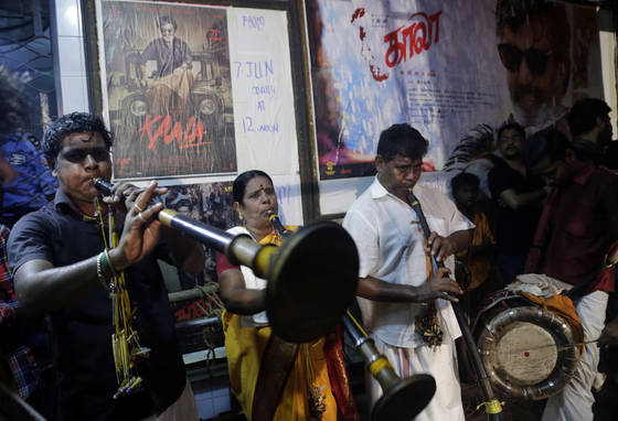 지난해 7월 7일, 인도 뭄바이의 한 영화관에서 인도 영화계의 수퍼스타 라지니칸트가 출연한 신작 영화 개봉에 맞춰 극장 안에서 음악을 연주하고 있다. [AP=연합뉴스]