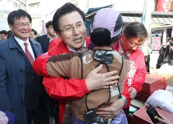황교안 자유한국당 대표와 정점식 통영·고성 보궐선거 후보가 22일 오후 경남 통영시 중앙동 통영중앙시장을 찾아 상인과 포옹을 하고 있다.[뉴스1]