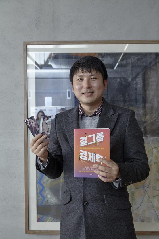 유성운 작가가 자신의 책 '걸그룹 경제학', 소녀시대 멤버 윤아·서현 포토카드를 들어 보였다. 그는 지난 2017년 소녀시대 데뷔 10주년을 맞이해 소녀시대 등 아이돌 그룹의 영향을 데이터로 증명한 책을 펴냈다.