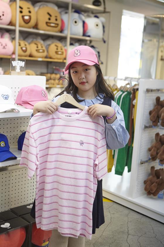 맹서후 학생기자가 BT21 캐릭터 '쿠키'가 있는 모자를 쓰고 티셔츠를 들어 보였다. 잘 만든 굿즈 하나는 다양한 형태로 퍼져 나간다.